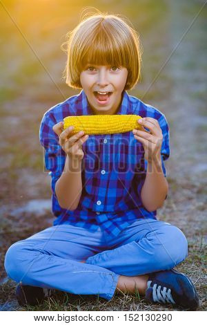 Happy boy eating healthy corn on the cob.