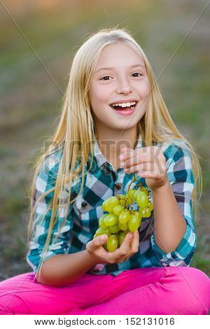 Happy smiling girl eating healthy grapes outdoor.