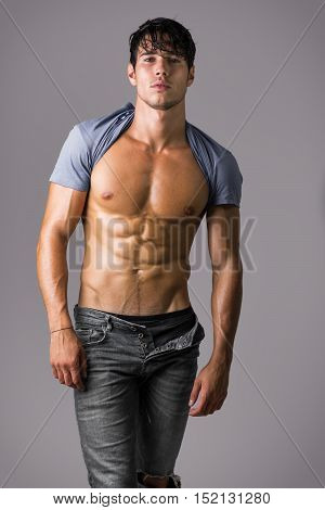 Portrait of naked handsome young man with languishing look wearing only jeans and a t-shirt pulled behind his head