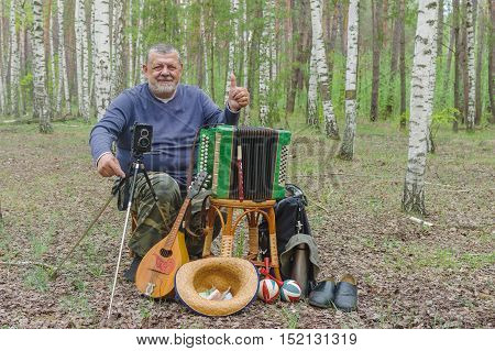 Happy senior camper is having rest in birch forest sitting on a wicker stool and holding mandolin