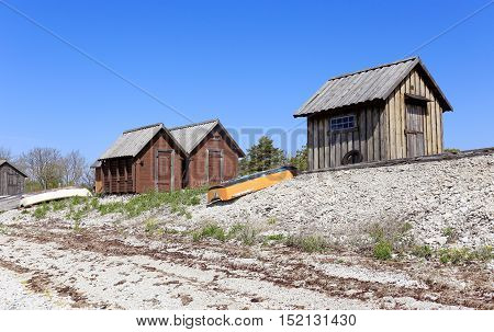 Blase, Sweden - May 13, 2016: Old fishing sheds and small boats at the beach in Blase on the Swedish island Gotland.