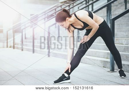 Be flexible. Athletic young beautiful girl stretching while warming up and preparing for training.