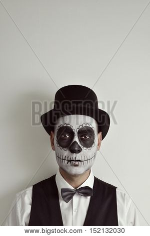 portrait of a man with a mexican calaveras makeup, wearing waistcoat, bow tie and top hat, against an off-white background