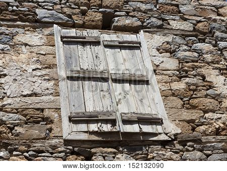 The wall of the old prison closed window with bars on the escape of criminals