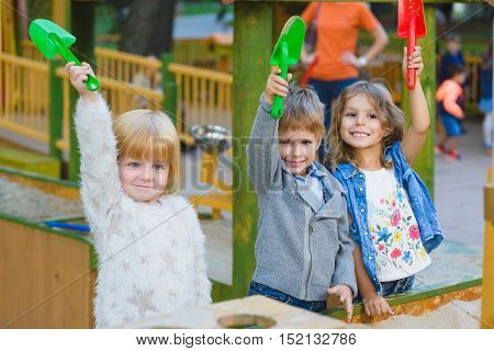 group of happy children playing in sandbox at playground.