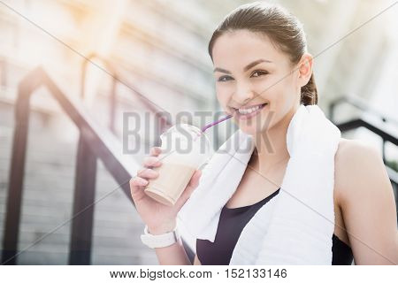 Cheerful relaxation. Attractive young woman smiling and having a drink after exercising in an urban setting.