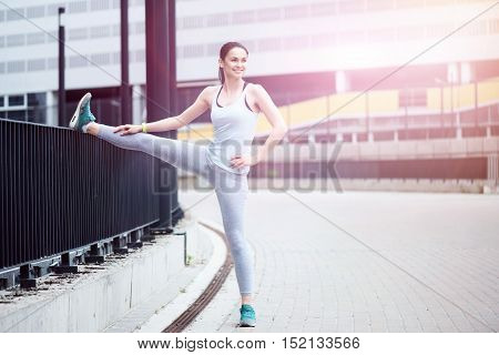 Happy fitness. Joyful young beautiful woman smiling and raising her leg while stretching in an urban setting.