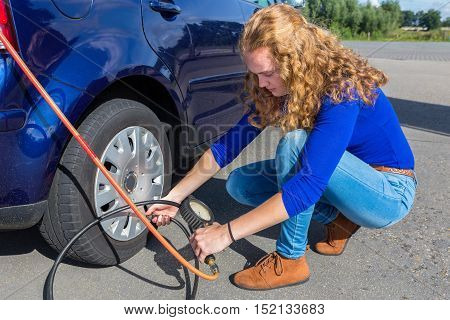Female driver checking air pressure of car tire outdoors