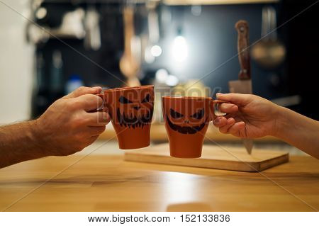 A couple celebrating halloween holding a mug with a drink with people scary pumpkin Jack-o'-lantern.