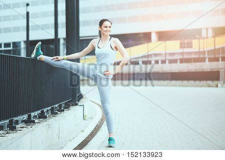 Joyful training. Slim cheerful beautiful woman smiling and stretching while working out in an urban environment.