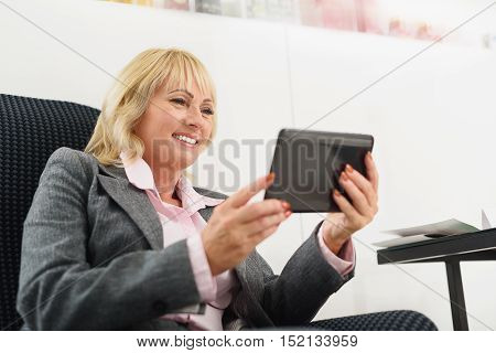 Happy senior woman is waiting for treatment in wellness center. She is sitting on chair and smiling. Lady is holding tablet and looking at screen with joy