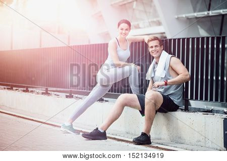 Enjoyable fitness. Joyful athletic couple smiling and relaxing together after working out in an urban environment.