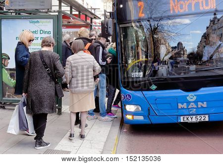 Stockholm, Sweden - April 21, 2015: A blue M.A.AN city bus on line 2 with destination Norrtull has stoped at tthe bus stop Stureplan where waiting people boarding the bus.