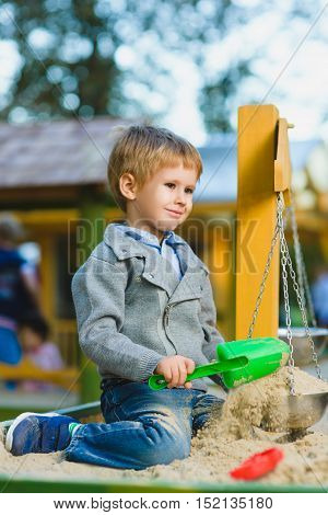 happy little boy playing in sandbox at playground.