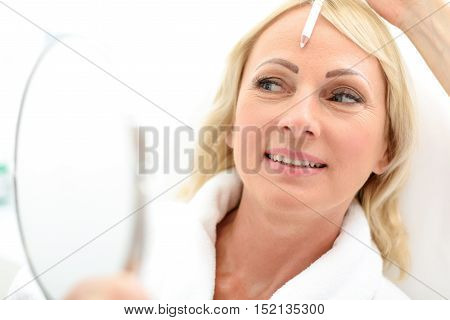 Happy senior woman is looking at her skin and smiling, She is sitting and holding mirror. Beautician hand is holding white pencil near female forehead