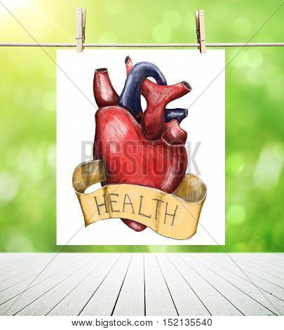 Paper sheet with creative heart sketch suspended on clothesline above wooden plank surface on blurry green background. Health concept