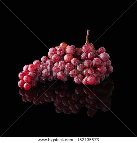 Bunch of red grapes isolated on a black glossy background with realistic reflection