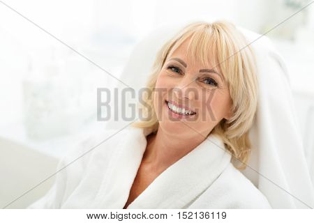 Happy mature woman is relaxing at spa salon. She is looking at camera and smiling. Woman is sitting in white bathrobe