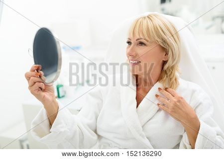 My skin is wonderful after this procedure. Joyful senior woman is looking at mirror and smiling. She is sitting on comfortable chair at wellness center