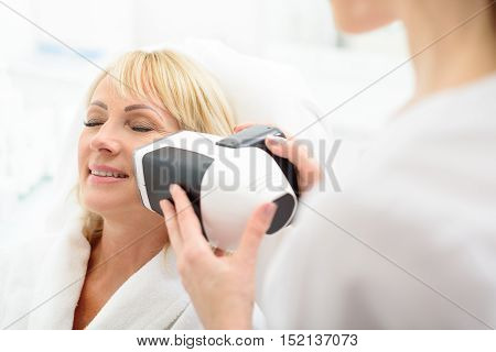 Professional beautician is touching female face by modern laser massager. Senior woman is relaxing and smiling