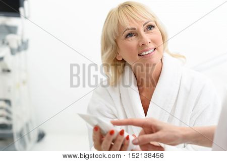 This cream is wonderful. Beautician hand is pointing finger at tube confidently. Mature lady is smiling and looking at cosmetologist with trust