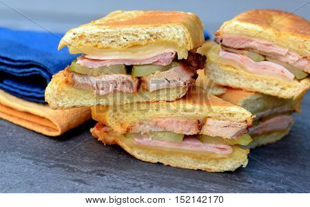 Cubano (Cuban Sandwiches): Close up of stacked sandwiches showing layered ingredients - ham, pork, Swiss cheese, pickles and mustard.