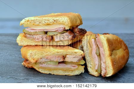 Cuban Sandwiches shown on a grey background. Side view, close up. Layered ingredients showing; pork, ham, Swiss cheese, pickles and mustard.