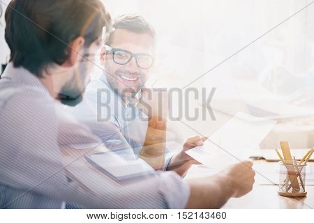 Good bargain. Handsome bearded man wearing glasses holding important document together with his business partner in modern office full of light.