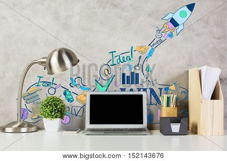 Front view of workplace with creative rocket ship sketch blank laptop screen supplies plant and other items. Mock up Start up concept
