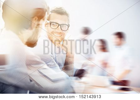 Business concept. Double exposed photo of young bearded man wearing glasses looking at his business partner on background with blurred people.