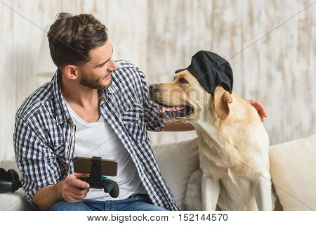 cool dog in a baseball cap looking at its owner with a smartphone