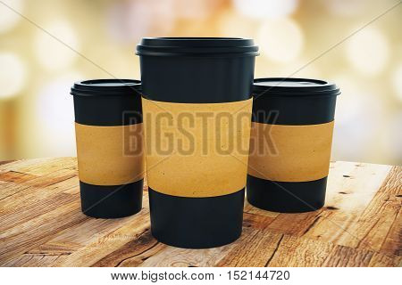 Close up of three black take away coffee cup with blank brown paper holder placed on wooden table. Light bokeh background. Mock up 3D Rendering
