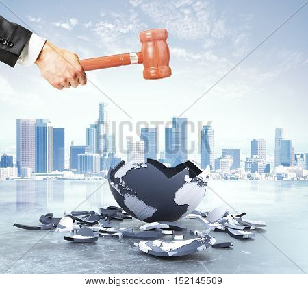Businessman hand cracking terrestrial globe with wooden hammer on city background. World destruction concept. 3D Rendering
