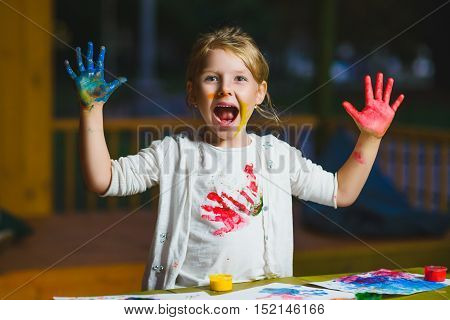 Child having fun painting with finger paint.