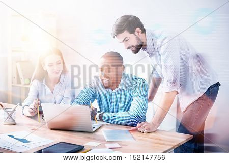 Young specialists. Photo of lively young-looking people working together on new laptop in light office, photo with blur and film effect.