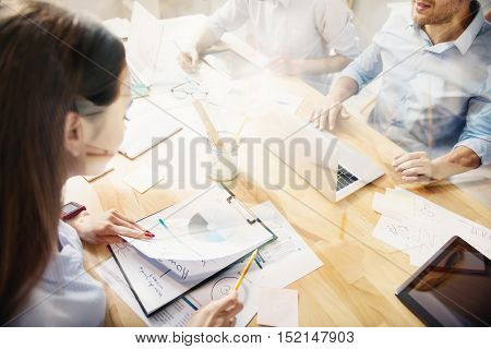 Checking on accuracy. Top view of young woman with long hair holding folder with papers and pencil in light office, together with her male colleagues.