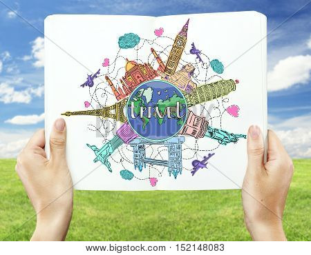 Close up of hands holding open book with creative colorful travel sketch on landscape background. Traveling concept