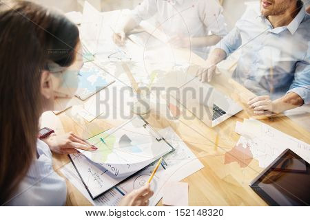 Preparing big project. Top view of young woman busy in office together with coworkers in light modern office behind worldwide connection interface.