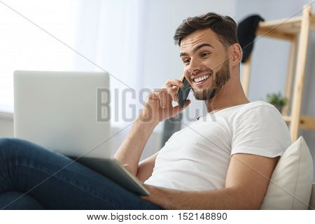 handsome guy talking on the phone an looking into laptop