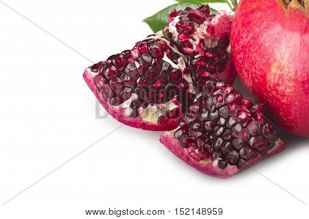 ripe pomegranate fruit and its grains on white background