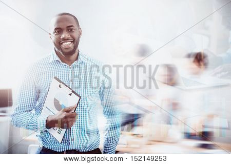 Project is finished. Portrait of young handsome bearded man standing with folder on background of blurred effect and virtual screen.