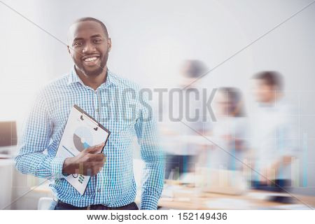 Ready to start. Handsome bearded guy smiling and holding folder with some infographcs on it in front of blurred effect and virtual screen.