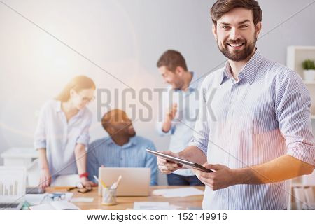 Working development. Young smiling bearded man standing on background of working colleagues with tablet in light office.