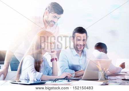 Team work. Bearded man standing above two young workers using laptop in light office.