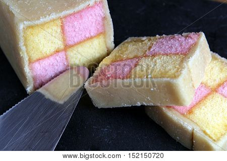 Freshly Cut Battenberg Cake On Dark Slate Background With Cake Slice. Pink And Yellow Sponge Covered
