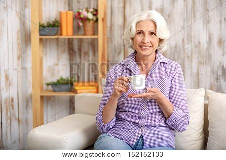 Joyful mature woman is enjoying hot tea and smiling. She is sitting on sofa with relaxation