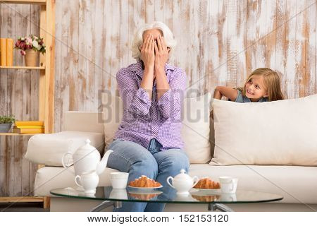 Friendly family is playing in hide and seek. Mature grandmother is sitting on sofa covering her face by hands with anticipation. Girl is hiding behind couch and smiling