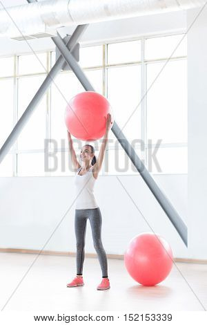 Staying fit. Cheerful confident slim woman standing in a gym and holding a fitness ball up while doing a physical exercise