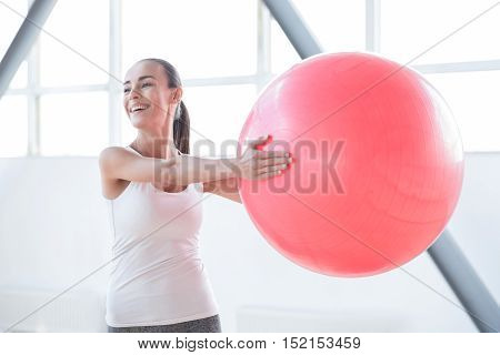 Using sports equipment. Positive delighted attractive woman standing in the gym and smiling while holding a fitness ball