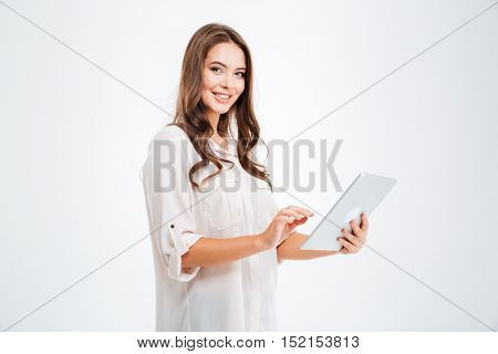 Portrait of a happy brunette woman using tablet computer isolated on a white background